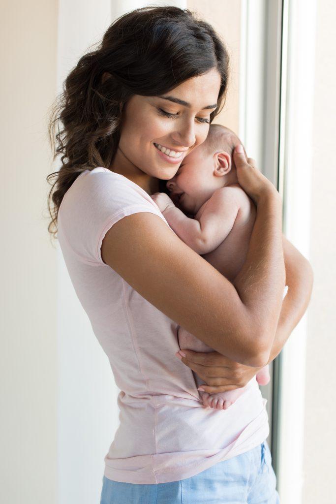 Mom Lovingly Hugging her baby by window on Breastfeeding School www.breastfeedingschool.com by Haydee Montemayor